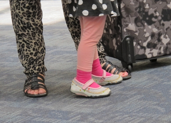 Mother and daughter wait for airplane at SFO. The girl wears pink socks, her mother wears camouflage pants. PHoto by Barbara Newhall