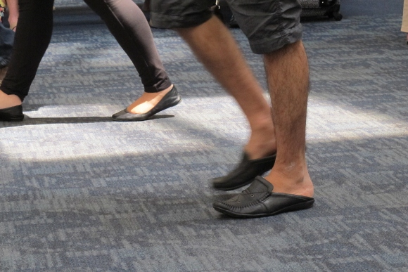 Man at SFO wears baggy shorts, slip-on shoes and hairy legs. Photo by Barbara Newhall