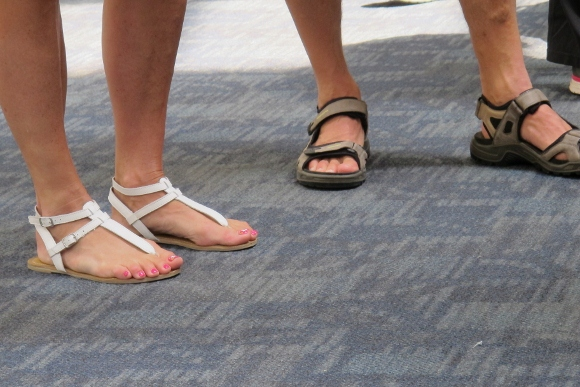 A woman wears delicate tan sandals, a man wears clunky hiking sandals at SFL. Photo by BF Newhall