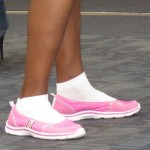 A young woman at SFO wears bright pink slip-on sneakers with bright white socks. Photo by Barbara Newhall