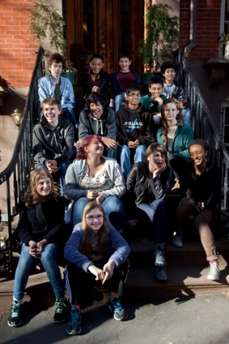 A dozen or so happy teenagers sit on the front steps of a brick building. The editorial board of KidSpirit meets to discuss future issues. Photo c 2014 by Jon Hochman