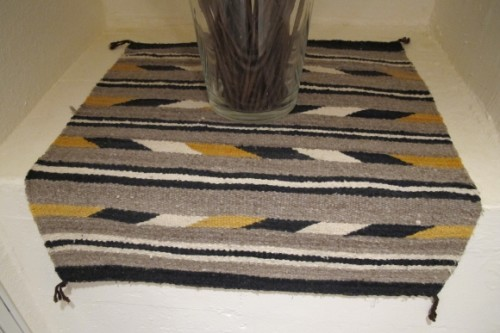 A small, coarsely woven Navajo rug of grey, black and gold. Photo by Barbara Newhall