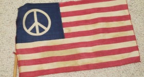 A 1960s era American flag with the peace symbol on a blue field where the stars would normally be. Photo by Barbara Newhall