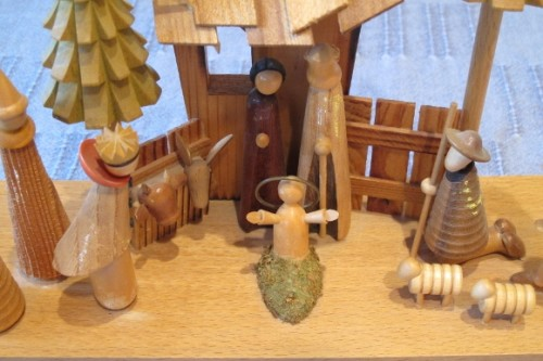 A Christmas nativity scene of hand-carved wood with open armed baby Jesus. Photo by Barbara Newhall