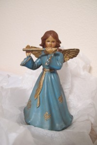 A plastic angle with a blue gown plays a golden flute. Photo by Barbara Newhall