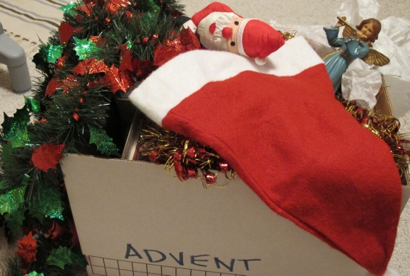 A box marked Advent overflows with Christmas decorations, including an angel, a Santa and shiney tinsel garlands. Photo by Barbara Newhall