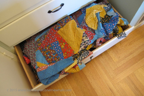 An unfinished quilt and stray piece of calico overflow from a storage drawer. Photo by Barbara Newhall