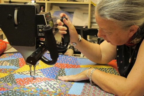 Sue Mary Fox quilting stitches a crazy quilt -- quilt top, batting and backing -- with her long arm sewing machine in her Berkeley, CA, studio. Photo by Barbara Newhall