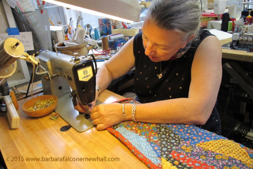 Sue Mary Fox hems a colorful calico crazy quilt on a sewing machine in her Berkeley, CA, studio. Photo by Barbara Newhall