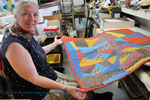 Sue Mary Fox shows off the calico quilt that she stitched together and quilted for a client. It is Barbara Falconer Newhall's crazy quilt. Photo by Barbara Newhall