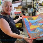 Sue Mary Fox with the colorful calico crazy quilt she completed in her Berkeley studio for Barbara Falconer Newhall. Photo by Barbara Newhall