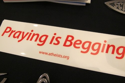 "A bumper sticker offered at the Religion Newswriters Conference in 2014 reads ""Praying Is Begging."" Photo by Barbara Newhall"