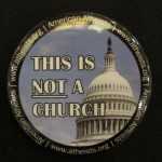 "A button displaying the dome of a captol has the words ""This is not a church.: photo by Barbara Newhall"