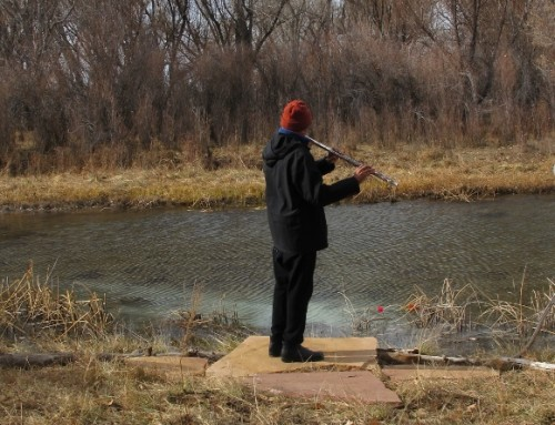 a man plays the flute by a small river in winter. Photo by Barbara Newhall