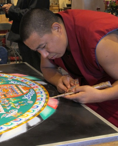 Yellow Hat Tibetan Buddhist monk grinds sand into the edge of a sand painting in Santa Fe NM. Photo by Barbara Newhall