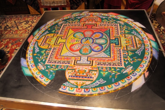 A sand painting created by the monks of the  Drepung Loseling Monastery of the Geluk school of Tibetan Buddhism that depicts the Immovable Buddha is partly destroyed by accident when a visitor drops her cell phone onto it. Photo by Barbara Newhall