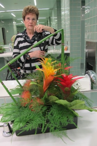 Members of the Flower Committee of the Fine Arts Museums of San Francisco created floral designs to decorate the ladies room at the DeYoung Museum for the 2015 Bouquets to Art Show. Author Barbara Falconer Newhall takes a selfie in the mirror. Photo by Barbara Newhall