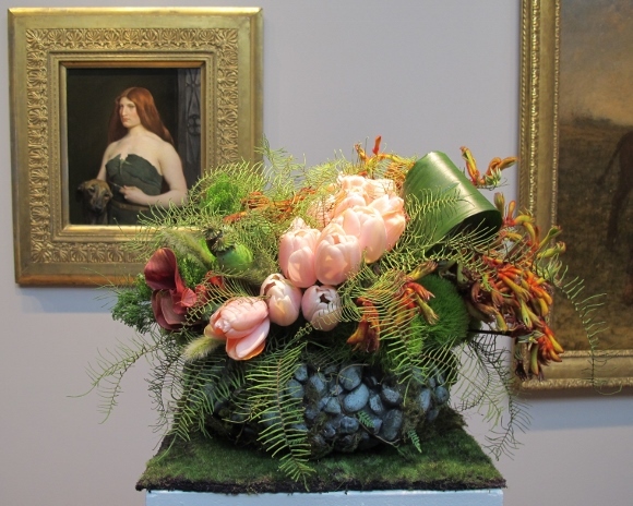 "Floral design at the FAMSA Bouquets to Art exhibition 2015 by Andrea Frenkel of Ukiah, CA. Lily and Mint.  the design complements George DF Brush's 1890 painting ""A Celtic Huntress."""
