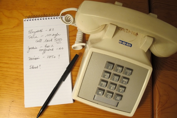An ivory colored touch-tone telephone, c.irca 1980s, with coiled cord and handset. A babysitter phone list is next to it. Photo by Barbara Newhall
