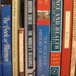 a bookshelf of books from many religions, including buddhism, taoism, christianity, judaism and islam. Photo by Barbara Newhall