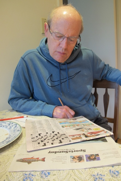 Retired and enjoying himself, Jon Newhall works on the New York Times Sunday crossword puzzle as it appears in the San Francisco Chronicle. Photo by Barbara Newhall