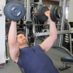 Man in his 30s lifts dumbells while semi reclined on bench. Photo by Barbara Newhall