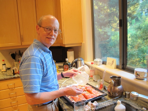 politics of housework. Jon cheerfully prepares salmon for a birthday dinner for his wife. Photo by Barbara Newhall