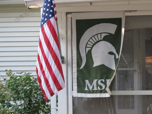 American flag flies next to a Michigan State University Trojans banner. Lots of Michigan State fans in Pentwater. Photo by Barbara Newhall