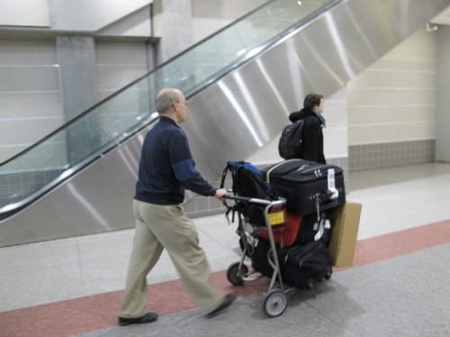 The politics of housework. A man pushes a cart stacked high with luggage at an airport. Photo by Barbara Newhall