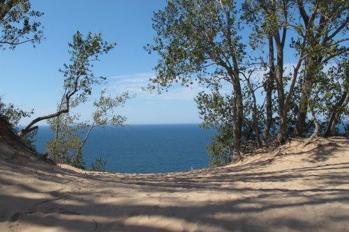"View of Lake MIchigan through trees atop a dune at Sleeping Bear Dunes National Lakeshore. Photo by Barbara Newhall. Barbara Falconer Newhall travels up and down Michigan's lower peninsula, visiting friends and family and putting on book events for ""Wrestling with God."""