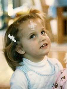 A toddler has a bandage on her forehead after hitting her head on a wall. PHoto by Barbara Newhall