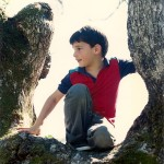 A lively 7-year-old boy who has climbed up in an oak tree. Photo by Barbara Newhall