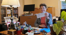 "Barbara Falconer Newhall, author of ""Wrestling with God: Stories of Doubt and Faith,"" with her first royalty check in her home office. Photo by Barbara Newhall"