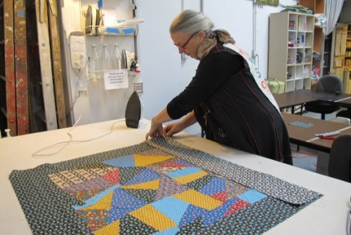 Sue Mary Fox in her Berkeley, California, quilting studio working on crazy quilt for Barbara Falconer Newhall. Photo by Barbara Newhall