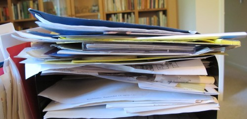 Papers stacked in a home office inbox -- like a spam-riddled email in-blox. Photo by Barbara Newhall
