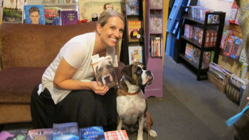 "Julie Hill Barton reads from her book, ""Dog Medicine,"" at A Great Good Place for Books, Oakland, CA. Here with a fan, Kirby, a brindle-haired boxer. Photo by Barbara Newhall"
