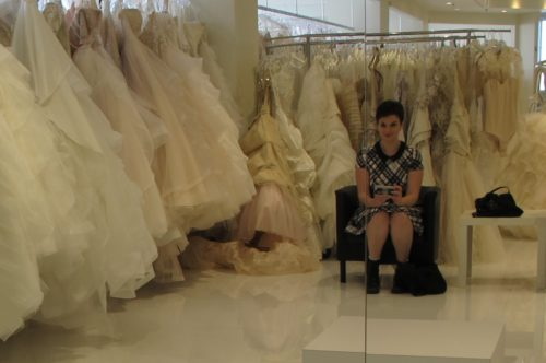 Bride in plaid dress contemplates an array of irvory wedding gowns at Le Marriage bridal shop, Los Angeles. Wedding dress shopping. Photo by Barbara Newhall