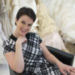 A bride wearing a plaid dress sits among frothy wedding dresses at Le Marriage, LA. Wedding dress shopping. Photo by Barbara Newhall