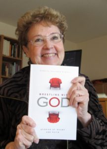Experiencing the shame of aging, author Barbara Falconer Newhall uses a copy of her book Wrestling with God, to cover her droopy chin as she approaches the Big Seven-Five. Photo by Barbara Newhall