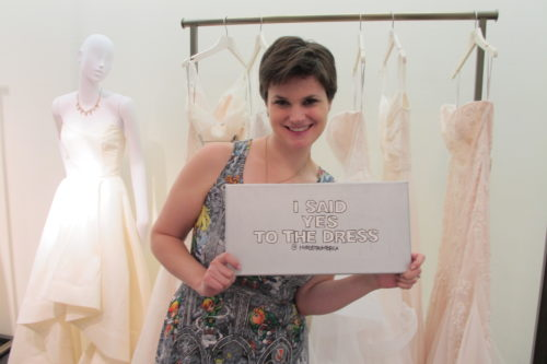 "A young bride celebrates choosing a wedding dress with a ""I said yes to the dress"" sign.. Photo by Barbara Newhall"