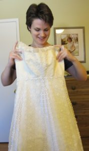 Christina Newhall holds up her mother's wedding dress for size. It's too small. Yes to the dress. Photo by Barbara Newhall