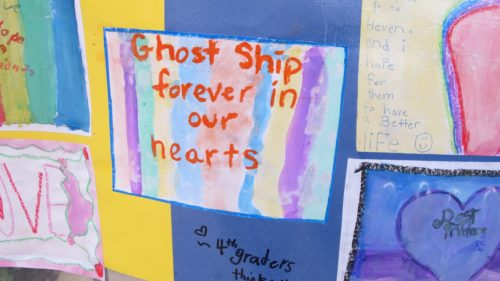A memorial banner by schoolchildren at the site of the Oakland Ghost Ship fire that killed 36 mostly young people, artists, musicians, LGBTQ folks. Photo by Barbara Newhall