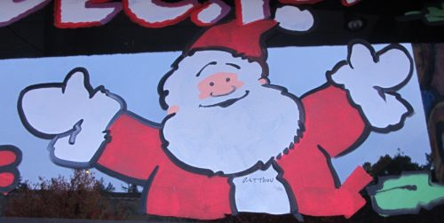 A cheery Santa Claus painted by Art Thou on a store window in Oakland, CA, 2016. Christmas is bigger than Christianity. Photo by Barbara Newhall