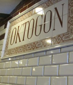 Up close shot of subway tiles in Budapest metro station with grimy grout and Oktogon station sign. Photo by Barbara Newhall