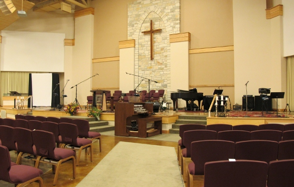The worship space of the First Evangelical Free Church of Austin with upholstered chairs in row, a simple cross at the front of the room and audio equipment set up for praise worship. Photo by bf newhall