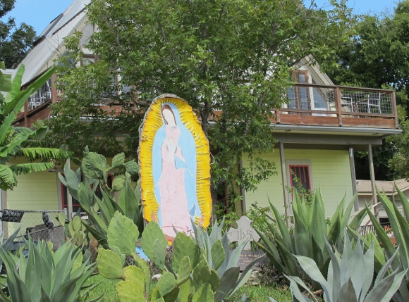 A sun-faded image of the virgin of guadalupe stands in an austin, tx, front yard next to a plaque honoring a soldier son who died in the Korean War. Photo by BF Newhall