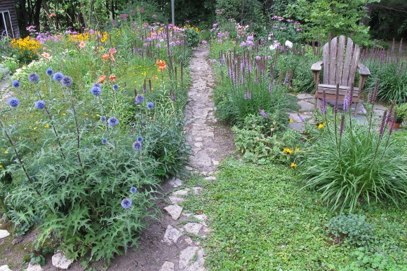 A weathered Adirondack chair sits in the midst of a profusely flowering garden with Liatris and day lilies. Photo by Barbara Newhall w